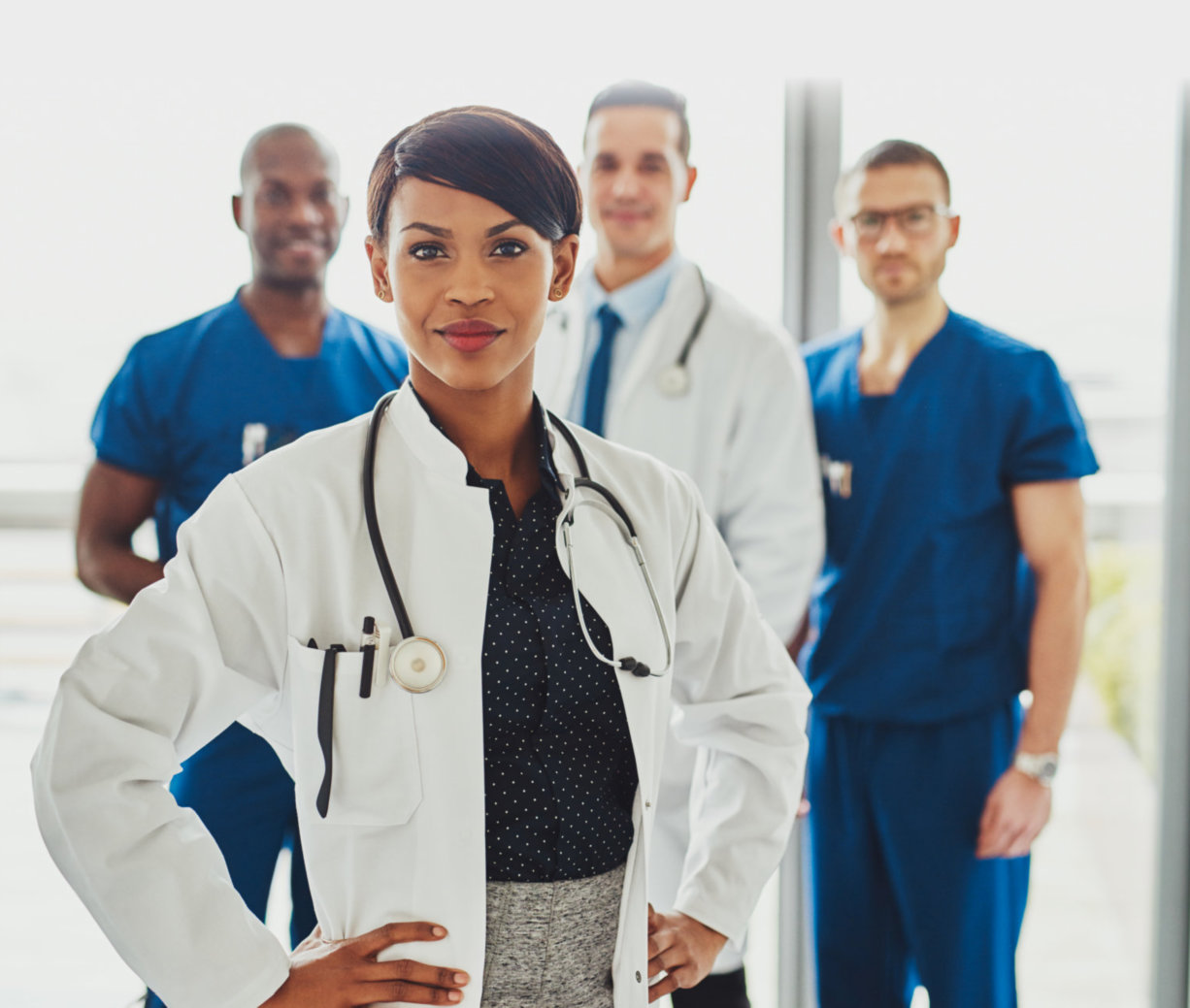four medical practitioners smiling