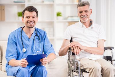 male nurse and senior man smiling at the camera